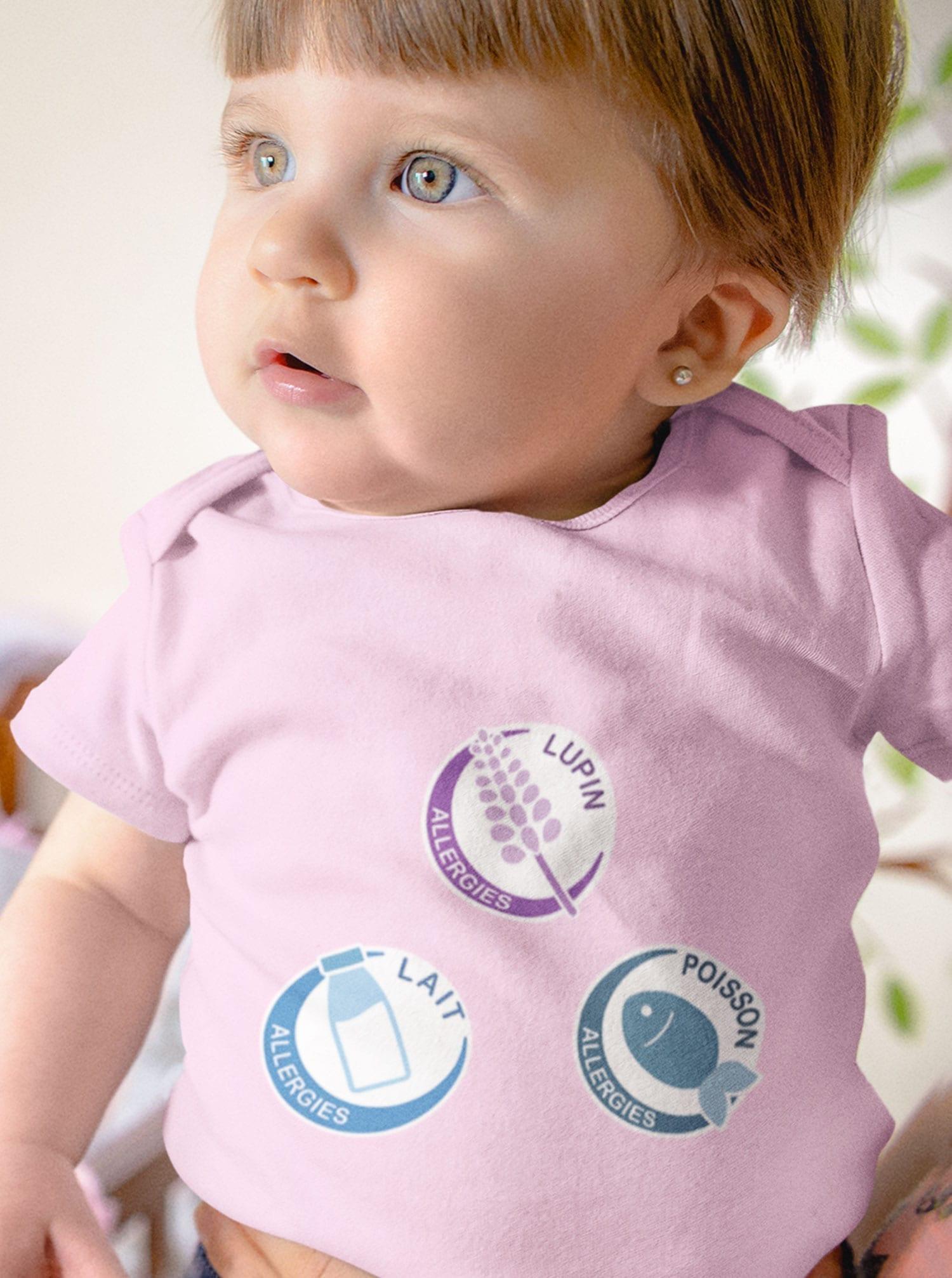 bébé fille en body rose affichant ses allergies alimentaires
